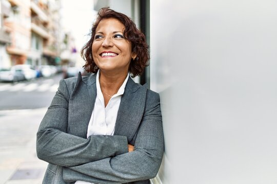 Middle age latin businesswoman smiling happy standing with arms crossed gesture at the city.