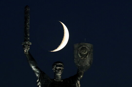 The waxing crescent moon sets behind the giant 'Mother of the Motherland' monument in Kyiv