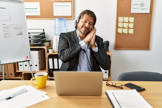 Handsome middle age man wearing call center agent headset at the office sleeping tired dreaming and posing with hands together while smiling with closed eyes.