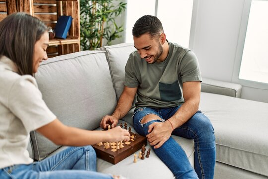Young latin couple smiling happy playing chess at home.