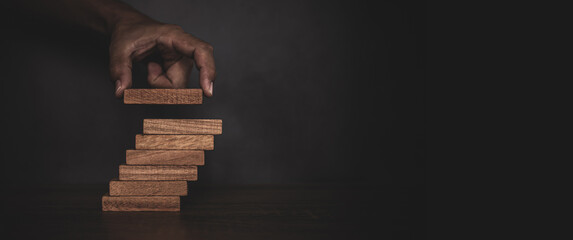 Obraz Close-up hand is placing wood block tower stacked in stair step with caution to prevent collapse or crash concepts of financial risk management and strategic planning. - fototapety do salonu