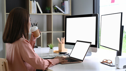Obraz Asian businesswoman drinking coffee and working wit multiple devices in office. - fototapety do salonu