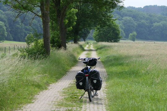 Wanderlust, a touring bike on a dirt road before the big trip between meadows in summer.