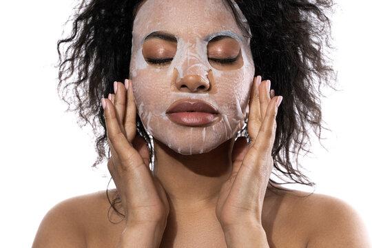 Beautiful black woman with a smooth skin applying facial sheet mask
