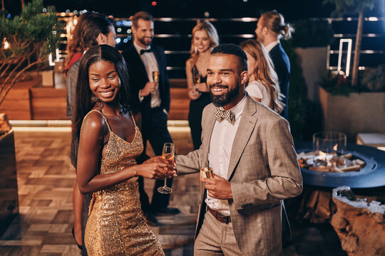 Beautiful young African couple in formalwear holding champagne flutes and smiling