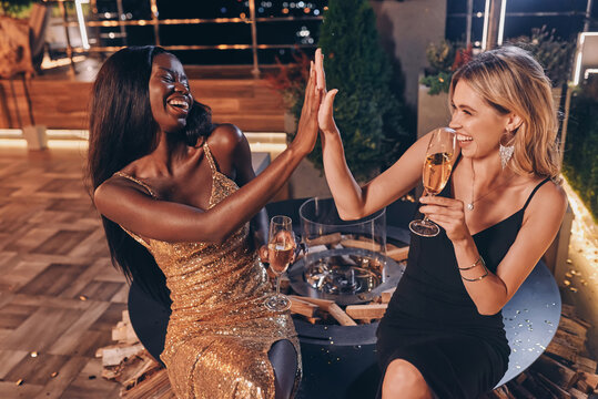 Two beautiful women in evening gowns communicating and smiling while spending time on luxury party