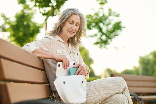 Elegant woman putting smartphone in her handbag
