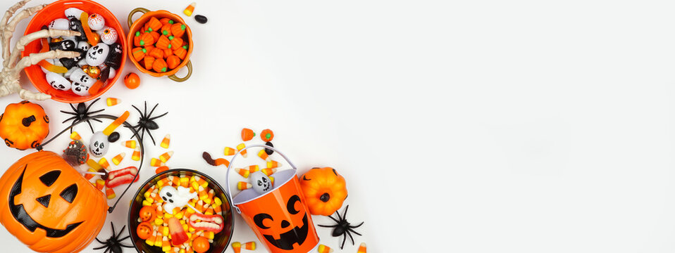 Halloween trick or treat corner border with jack o lantern pails and a selection of candy. Above view on a white banner background with copy space.