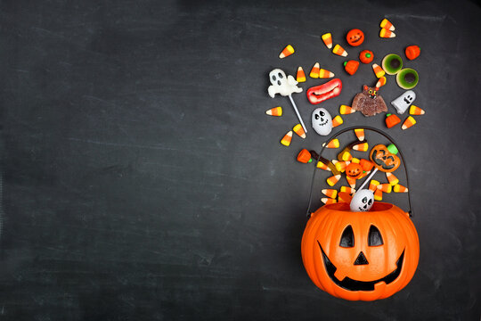 Halloween Jack o Lantern pail with spilling candy, top view on a black background with copy space