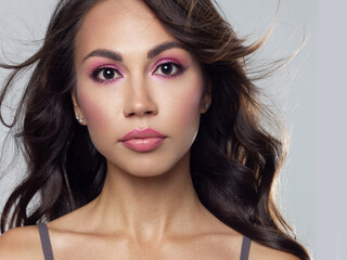 Beautiful brunet model woman face with brown eyes and perfect make-up . Portrait of beauty young...