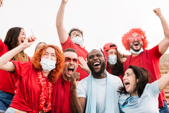 Group of happy multiracial football fans screaming while supporting their team at stadium and celebrating victory - Focus on black man