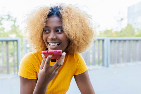 Joyful american young girl using cell phone in the street - Happy afro curly student sending voice message thought smartphone - Friendship, social media, youth and gen z concept