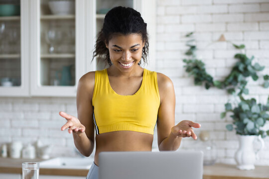 Happy african american woman fitness trainer talking online using laptop by video call with to her followers standing in the home kitchen