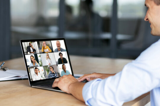 Group brainstorm concept, Caucasian employee uses laptop computer for online meeting with diverse multiracial colleagues sitting at the workplace