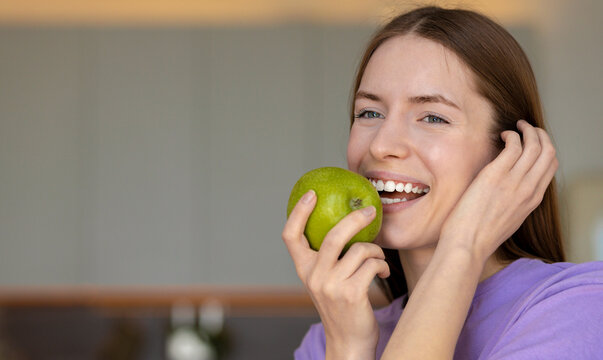 Portrait of beautiful young caucasian woman with white teeth smiling and eating a green apple, healthy lifestyle, copy space