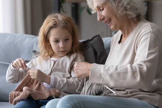 Smiling middle aged mature grandmother teaching adorable small child girl knitting stuff with needles and threads. Happy multigenerational female family involved in creative hobby activity at home.