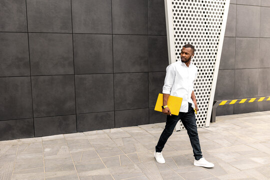 Confident male student or freelancer in stylish clothes standing with yellow laptop outdoors, walking to the office for business meeting. Serious successful businessman looking at the side, posing