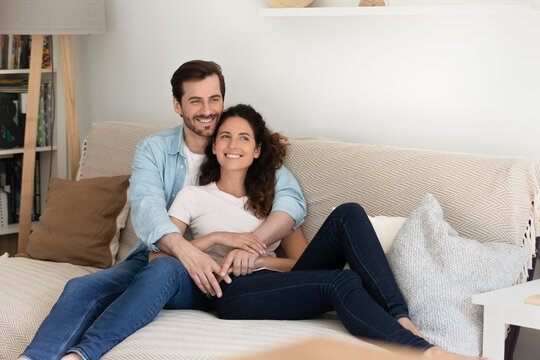 Beautiful millennial married couple hugging resting together on comfy sofa at home smiling looking into distance daydreaming enjoy wellbeing at first own apartment. Bank loan, happy homeowners concept