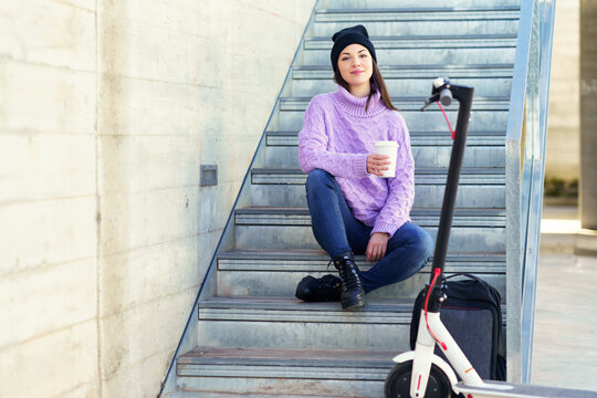 Female student with electric scooter taking a coffee break sitting on some steps outdoors