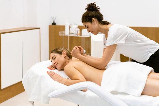 Female masseuse giving a back massage to a woman in a beauty parlour.