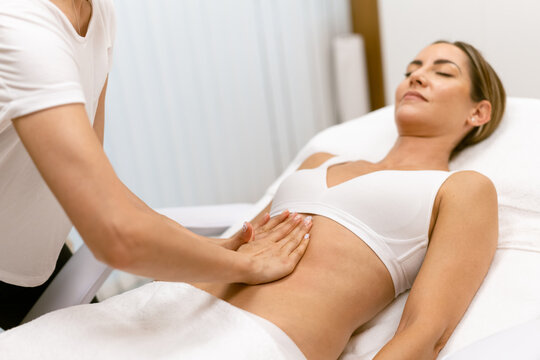Middle-aged woman having a belly massage in a beauty salon.