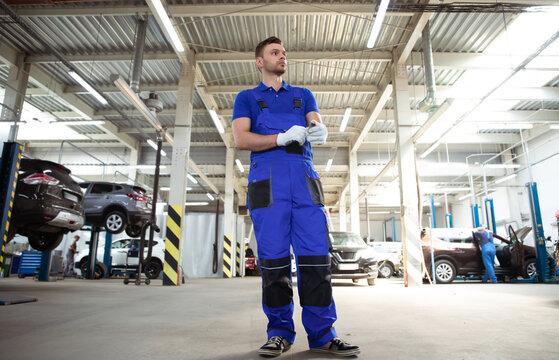 Confident handsome young and experienced car repair worker in work overalls posing against the background of lifted cars in a car service
