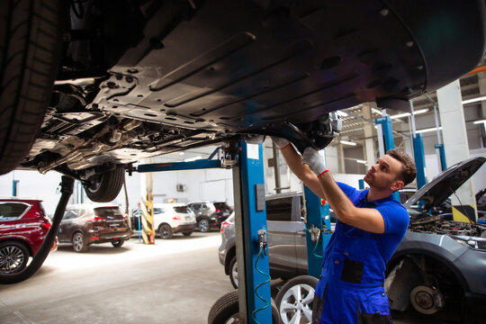 Cheerful, handsome, and confident car repair specialist in overalls repairs and replaces old parts with new ones in a car on a lift in service