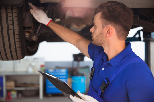 Confident and concentrated young and experienced car repair specialist with a tablet in his hand inspects and diagnosis the car for breakdowns