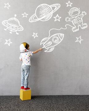 Happy kid draws a chalk rocket on the wall