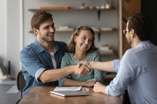 Smiling young Caucasian couple buyers clients shake hand of male real estate agent have meeting in office. Happy millennial man and woman handshake realtor buy rent house, make deal. Rental concept.