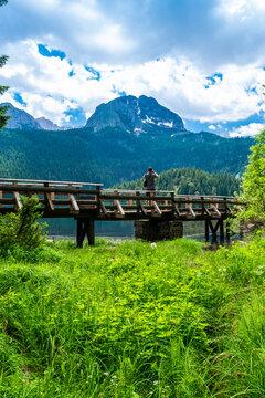Tourist man on wooden footbridge over stream and Glacial Black Lake. Durmitor National Park. Montenegro.