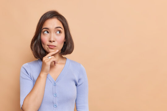 Thoughtful Asian woman keeps hand on chin looks pensively above dressed in casual blue jumper poses against brown background blank copy space for your advertising content thinks about future