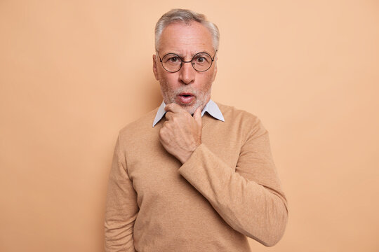 Portrait of surprised mature man holds chin reacts emotionally to news looks shocked at camera wears optical round spectacles casual jumper isolated over brown background. Human reaction concept