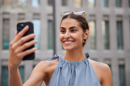 Beautiful stylish woman makes video call via smartphone while strolling in urban setting enjoys summer day has upbeat mood poses against blurred background. Pretty female model has online conversation