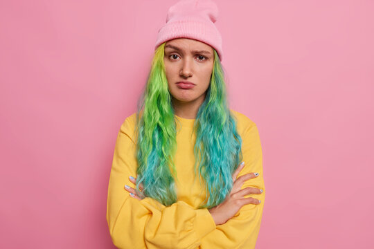 Upset offended woman keeps arms folded feels unhappy listens bad news dissatisfied while talking with interlocutor dressed in casual clothes poses against pink backgound has frowning disappointed face