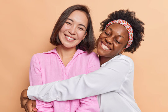 Diverse women embrace and have friendly relationship love each other dressed casually enjoy spending time together isolated over beige background. Reunion and international friendship concept