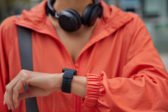 Unrecognizable woman checks fitness activity on smartwatch trains outdoors checks pulse and results after cardio workout uses headphones for listening music from playlist. Modern sport gadgets
