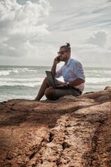 Cyfrowy nomada, człowiek pracujący z laptopem i smartfonem zdalnie na tle oceanu i skał...