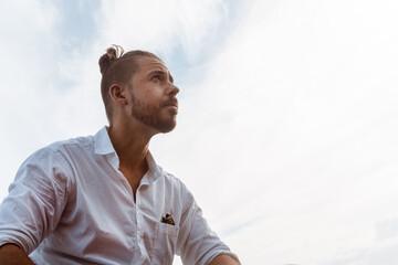 Fototapeta Portret mężczyzny ubranego w białą koszulę patrzący w niebo. obraz