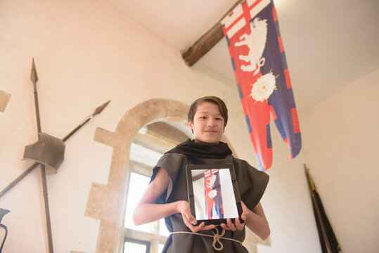 Portrait of history student with digital photograph of Richard III banner on digital tablet, Bolton Castle, 14th century Grade 1 listed building, Scheduled Ancient Monument