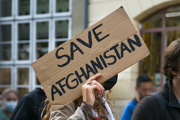 Fototapeta Female activist holding a cardboard sign with text Safe Afghanistan at a demonstration in Lubeck, Germany after the Taliban takeover obraz