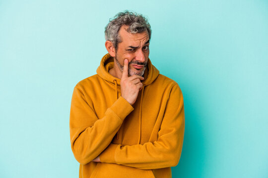 Middle age caucasian man isolated on blue background  contemplating, planning a strategy, thinking about the way of a business.