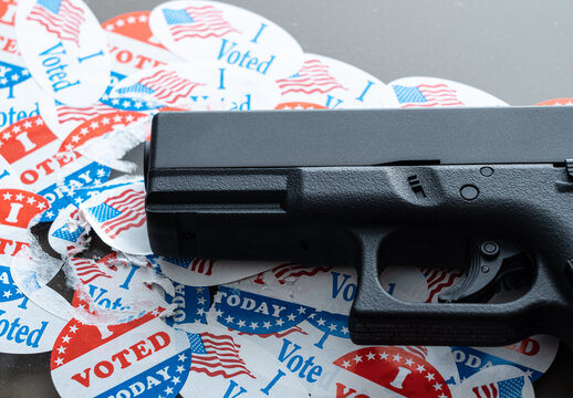 Concept for election violence with handgun placed on many torn and damaged voting stickers or buttons