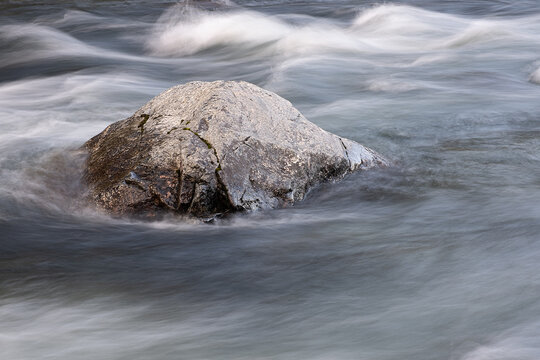 abstract background from long exposure of water stream in a mountain river close-up