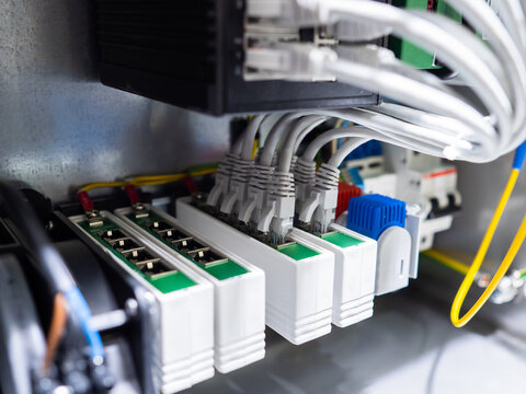 Network hardware. Internet cables are connected to switches. Network station. Fragment of structured cabling system. Internet equipment in metal box. Fragment of equipment control station