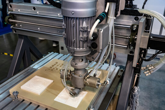 Milling equipment. Milling machine during work. Process of carving something out of wood. Machine during engraving. Cutting of plastic elements. Milling machine cuts out of white plastic.