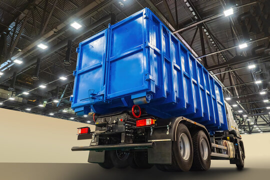 Blue truck. Truck under roof of hangar or warehouse. Car for transport of goods. Demonstration machines.  Garbage collection truck body. Demonstration of equipment for housing and communal services