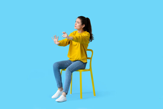 Young woman with imaginary steering wheel sitting in chair on color background