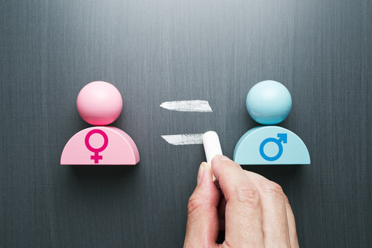 Concept image of gender equality. Female and male symbols. Hand writing equal sign on blackboard.