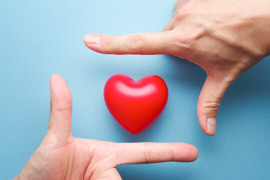 Healthy heart and mental. Heart and hand frame on blue background.